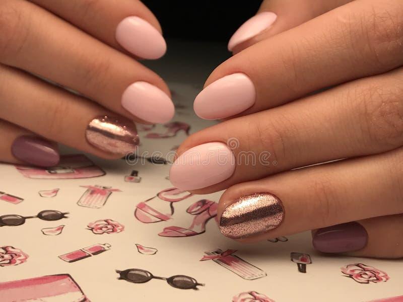 Os pregos cor-de-rosa bonitos com gel lustram e brilham fotos de stock