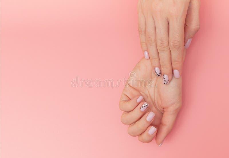 Os pregos da mulher bonita com tratamento de mãos à moda agradável no fundo cor-de-rosa fotografia de stock royalty free