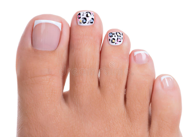 Os pregos da mulher bonita dos pés com tratamento de mãos francês bonito foto de stock