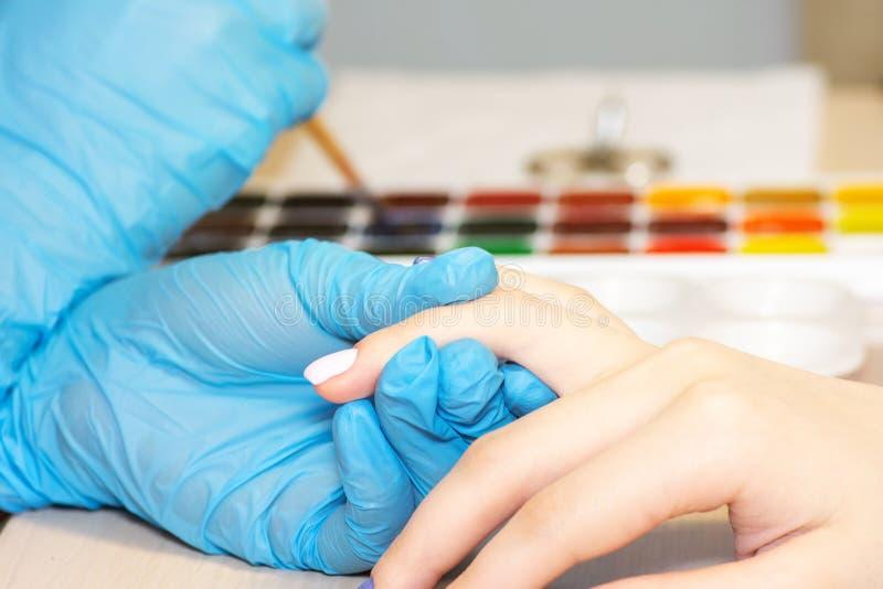 Os pregos da mulher natural saudável do close up no salão de beleza Pregos do cliente da pintura da mão do manicuro fotos de stock royalty free