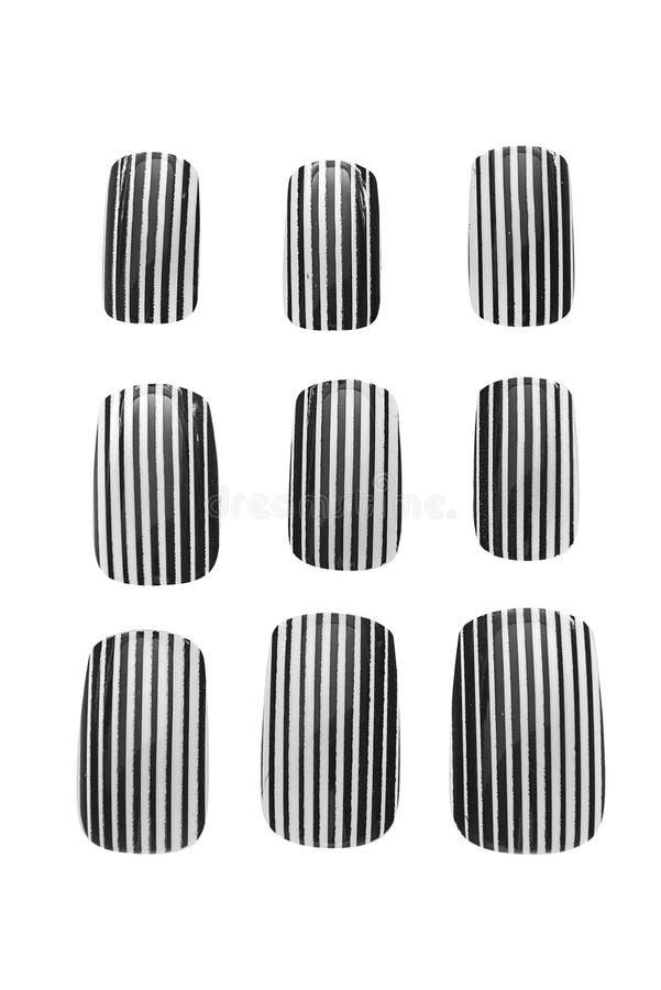 Os pregos falsificados pintados brancos e pretos das listras, isolados no fundo branco, trajeto de grampeamento incluíram foto de stock