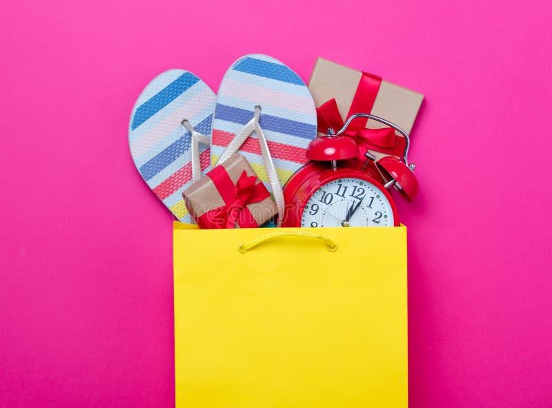 Os presentes bonitos, o despertador e as sandálias frescas no saco de compras e arrulham imagens de stock royalty free