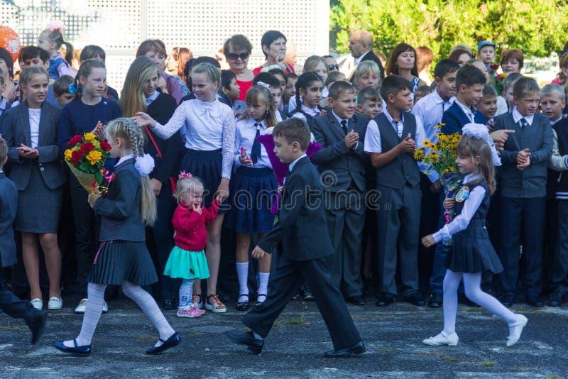 os Primeiro-graduadores com os ramalhetes das flores são na frente dos estudantes da High School no dia conhecimento do 1º de set fotografia de stock