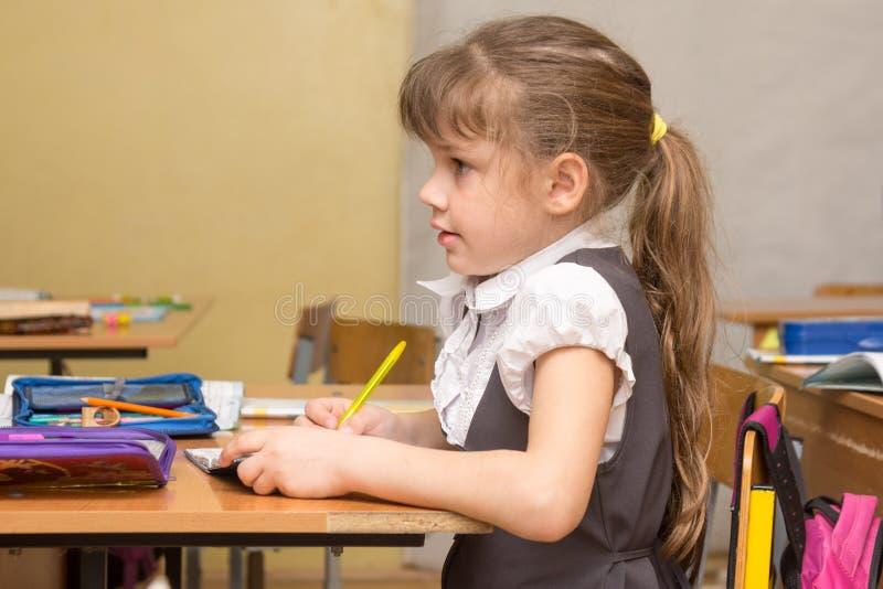 Os primeiro-graduadores de uma menina escutam atentamente o professor na escola fotografia de stock