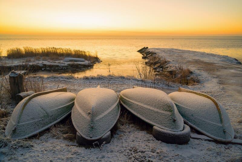 Os primeiros raios de sol sobre o lago Ladoga de manhã no inverno Barcos derrubados em uma praia de neve Região de Leningrado Pan fotos de stock