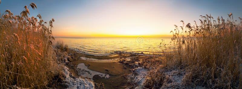 Os primeiros raios de sol sobre o lago Ladoga de manhã no inverno Região de Leningrado foto de stock royalty free