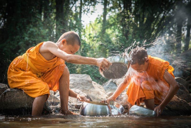 Os principiantes budistas estão limpando bacias e estão espirrando a água no s fotos de stock royalty free