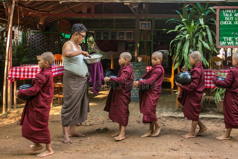 Os principiantes budistas novos andam para recolher a esmola e as ofertas nas ruas de Bagan, Myanmar fotos de stock royalty free