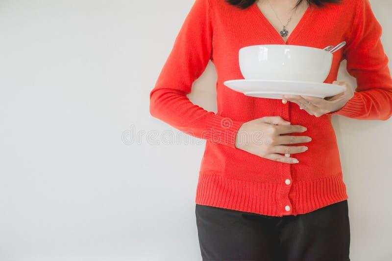 Os problemas da digestão, mulher com dor de estômago após comer, fêmea da mão que guarda sua barriga, não comem no tempo fotos de stock royalty free
