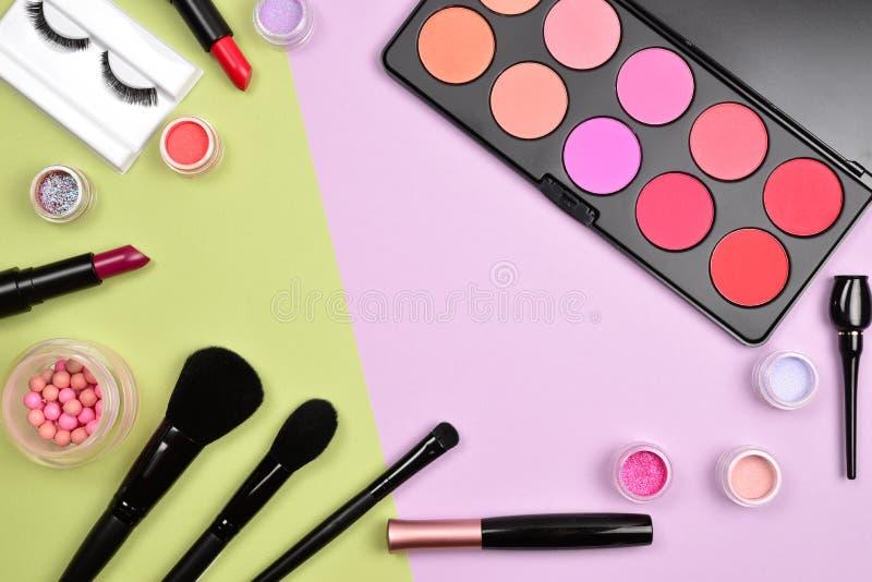Os produtos de composi??o profissionais com os produtos de beleza cosm?ticos, coram, forro do olho, chicotes do olho, escovas e f foto de stock