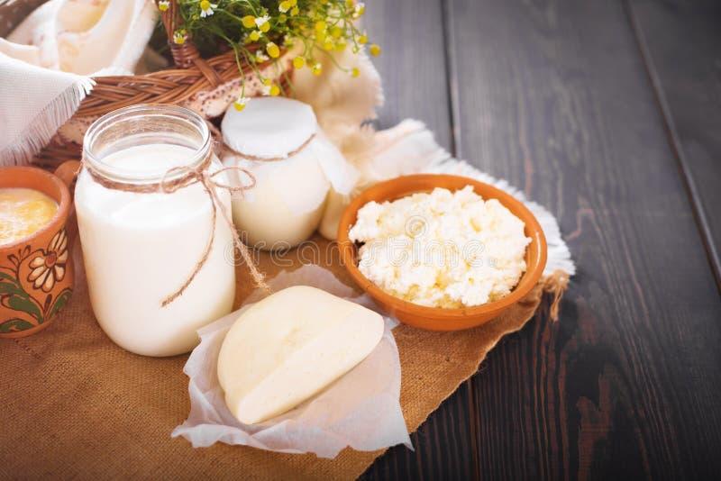 Os produtos láteos sortidos ordenham, iogurte, requeijão, creme de leite Ainda vida rústica fotografia de stock royalty free