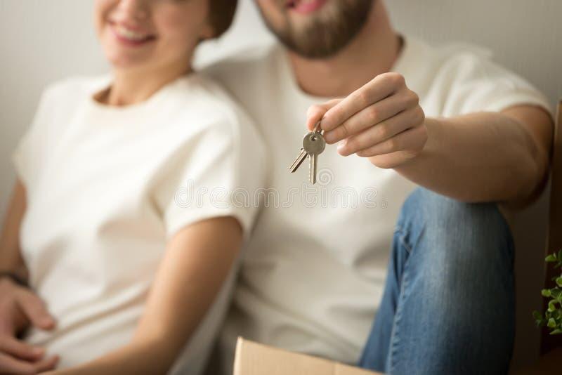Os proprietário novos felizes acoplam guardar as chaves da casa, fim acima da vista fotos de stock