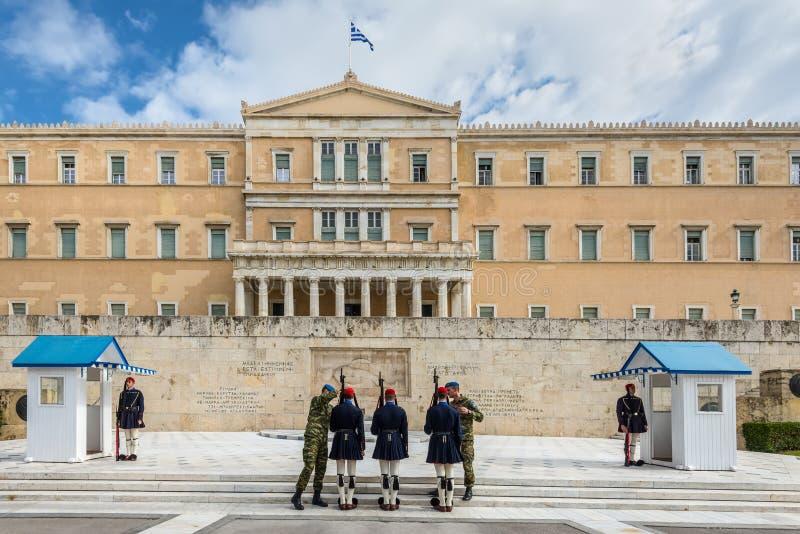 Os protetores cerimoniais presidenciais de Evzones guardam o túmulo do soldado desconhecido na construção grega do parlamento foto de stock royalty free