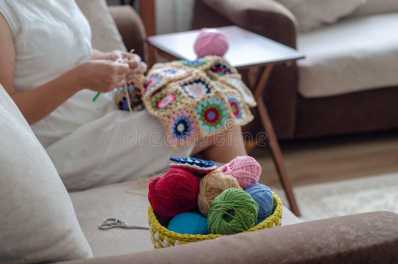 Os quadrados de manta coloridos do feito crochê em um assento e em uma mulher coloridos de creme estão fazendo crochê fotos de stock royalty free