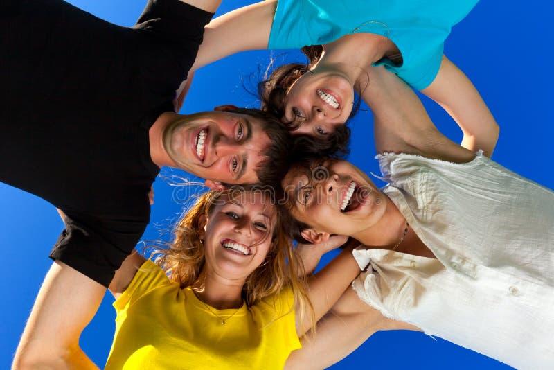 Os quatro amigos, abraçando, têm foto de stock royalty free