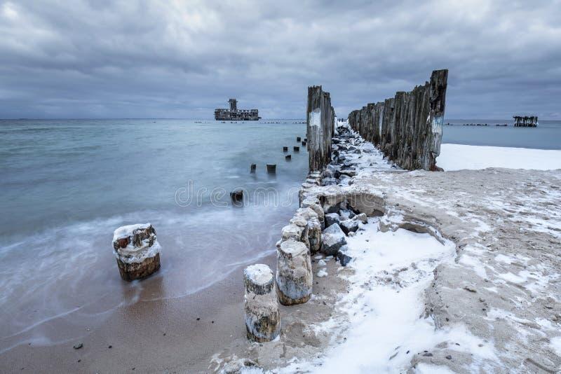 Os quebra-mares de madeira congelados alinham à plataforma do torpedo da segunda guerra mundial no mar Báltico fotos de stock