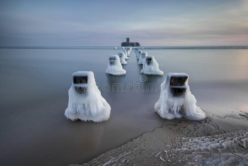 Os quebra-mares de madeira congelados alinham à plataforma do torpedo da segunda guerra mundial no mar Báltico imagens de stock royalty free