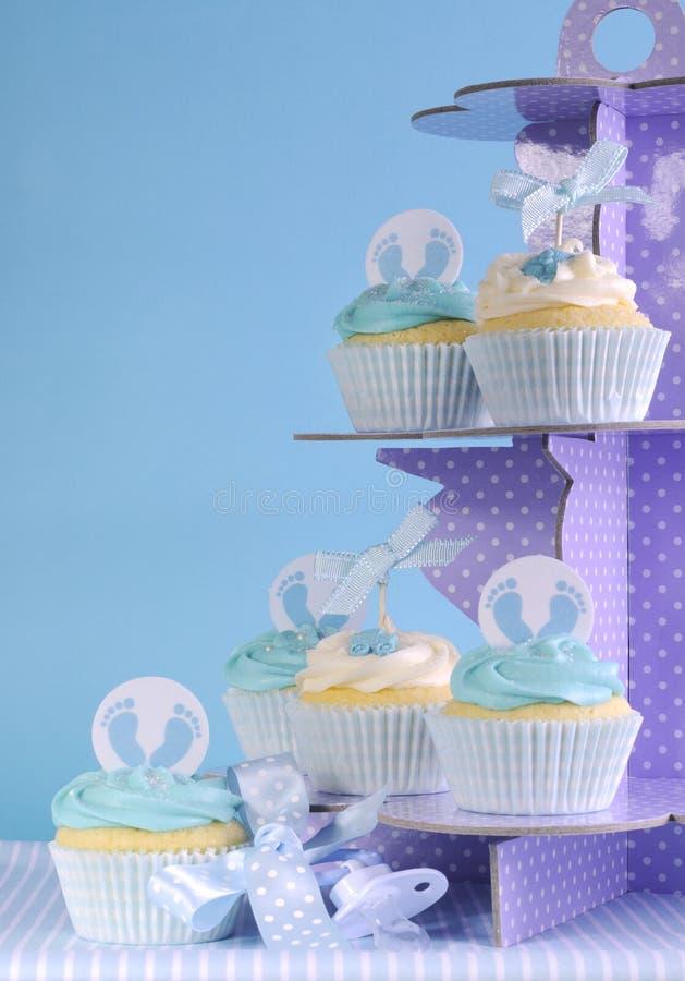 Os queques azuis do bebê do tema no queque roxo do às bolinhas estão imagens de stock
