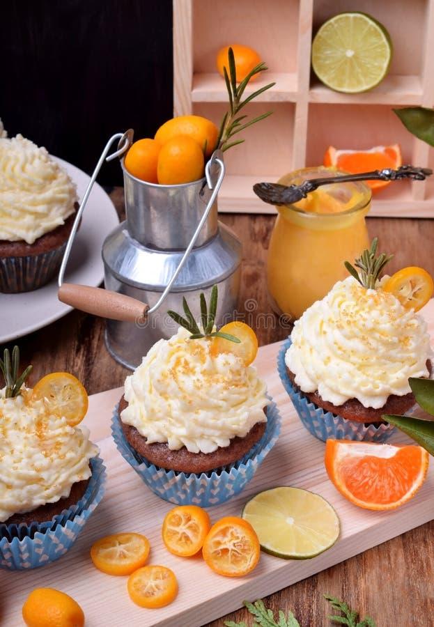Os queques cobriram com creme da manteiga, fatias de kumquat e alecrins imagem de stock