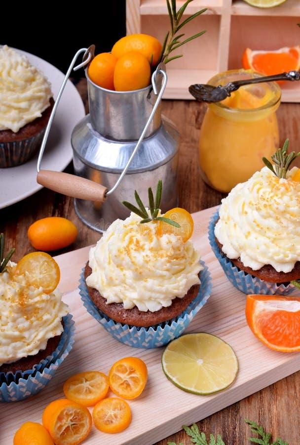 Os queques cobriram com creme da manteiga, fatias de kumquat e alecrins fotos de stock