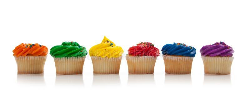 Os queques coloridos Assorted com polvilham no branco fotos de stock royalty free