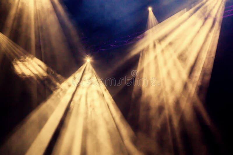 Os raios claros amarelos do projetor através do fumo no teatro ou na sala de concertos Equipamento de iluminação para um desempen fotografia de stock
