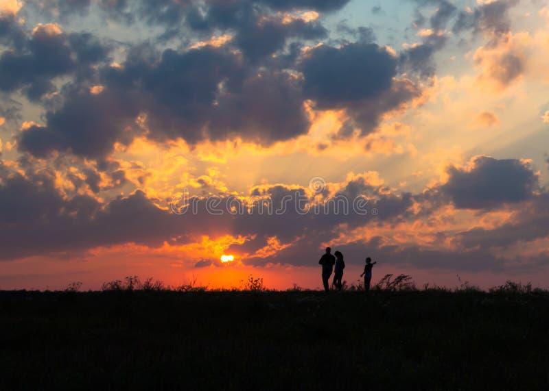 Os raios do sol do alvorecer do por do sol sobre o céu do campo colocam a família que anda perto do sol na silhueta do horizonte imagem de stock