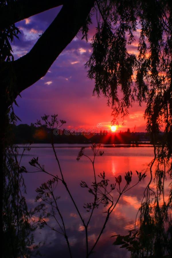 Os raios do sol vermelho refletiram na água de um lago Céu com as nuvens coloridas bonitas fotos de stock