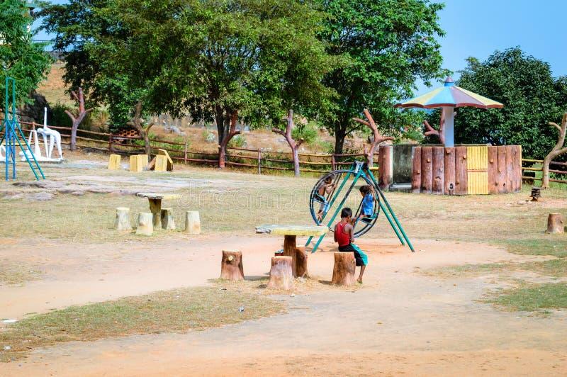 Os rapazes pequenos locais não identificados estão jogando em um parque da vila foto de stock royalty free