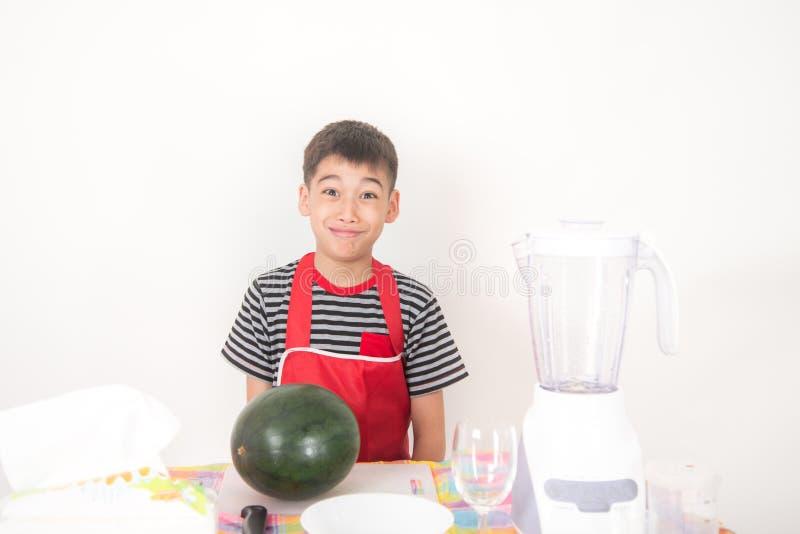Os rapazes pequenos misturam o suco da melancia usando o misturador imagem de stock royalty free