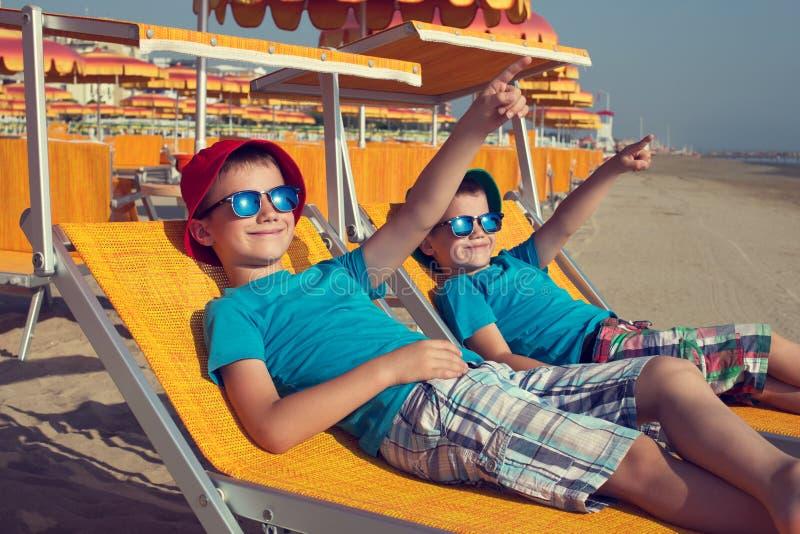 Os rapazes pequenos relaxam no deckchair que mostra afastado imagens de stock