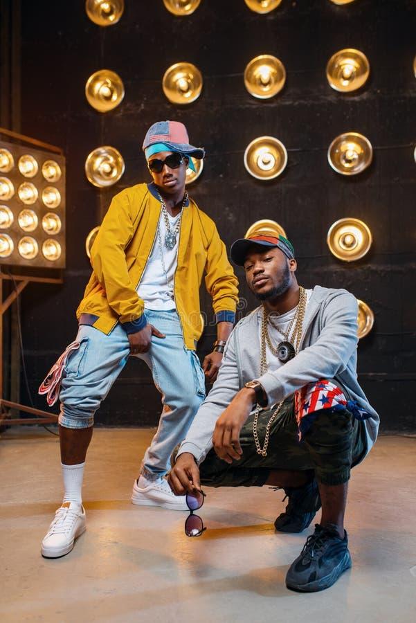 Os rapperes nos tampões dançam na fase com projetores foto de stock royalty free