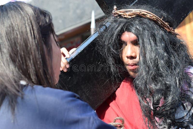 Os rasgos reais emitem-se dos olhos de Jesus Christ como a mulher vem próximo, drama da rua, a comunidade comemoram o Sexta-feira foto de stock royalty free