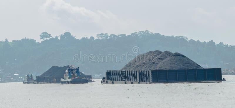 Os rebocadores puxam barcas carregadas pesadas do carvão fotos de stock