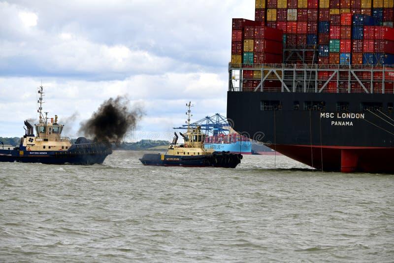 Os reboquees conduzem para fora um navio de recipiente do porto de Felixstowe Reino Unido fotos de stock