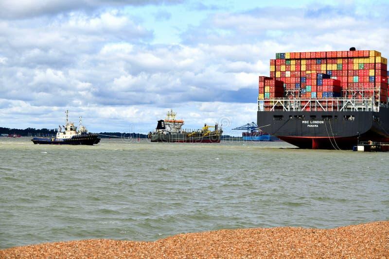 Os reboquees conduzem para fora um navio de recipiente do porto de Felixstowe Reino Unido fotografia de stock royalty free