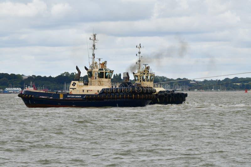 Os reboquees conduzem para fora um navio de recipiente do porto de Felixstowe Reino Unido foto de stock royalty free