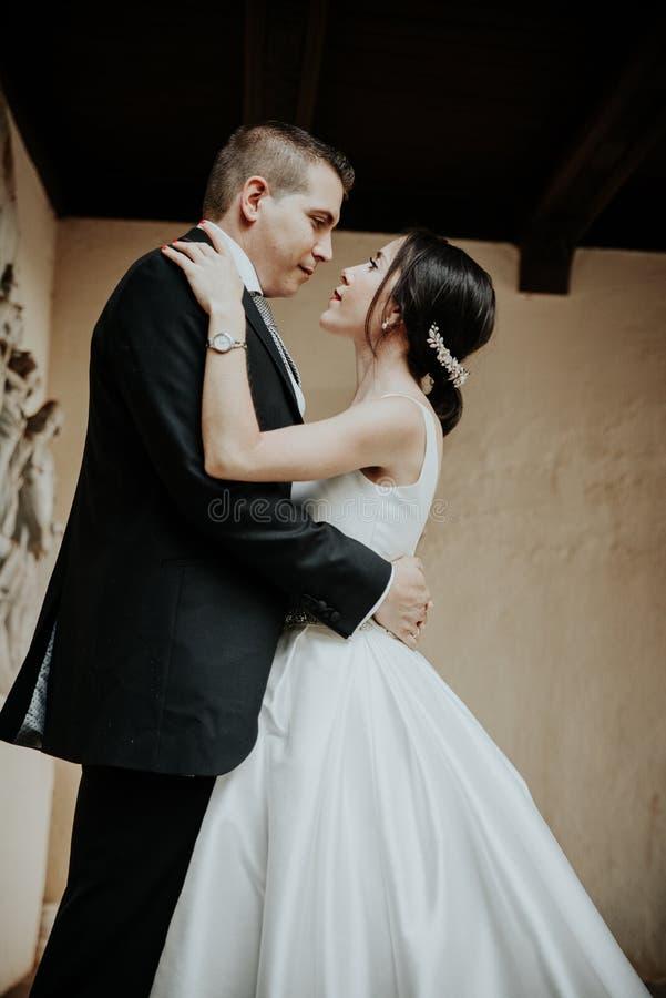 Os recém-casados abraçam e olham se Aperto da noiva e do noivo fotos de stock