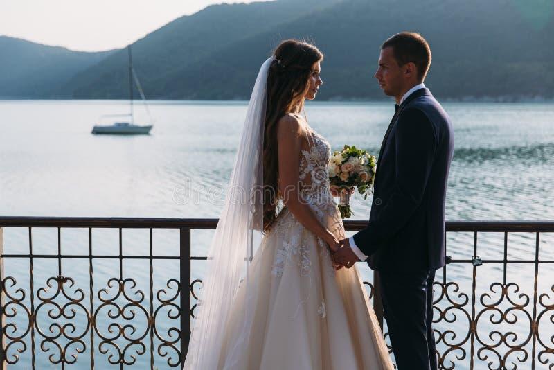 Os recém-casados acoplam-se, os noivos que mantêm as mãos olhadas em se os olhos do ` s em um fundo do lago Menina bonito no bran imagens de stock royalty free