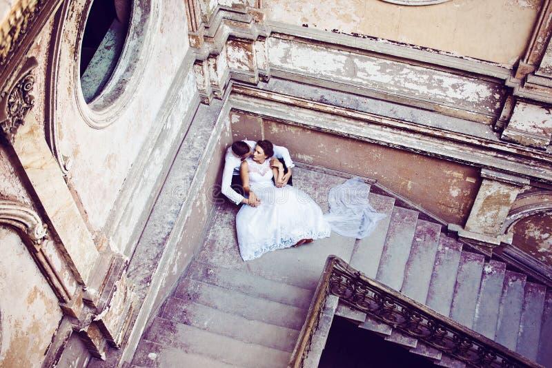 Os recém-casados aproximam escadas velhas foto de stock royalty free