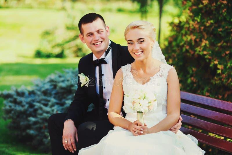 Os recém-casados de sorriso sentam-se no banco no parque fotos de stock royalty free