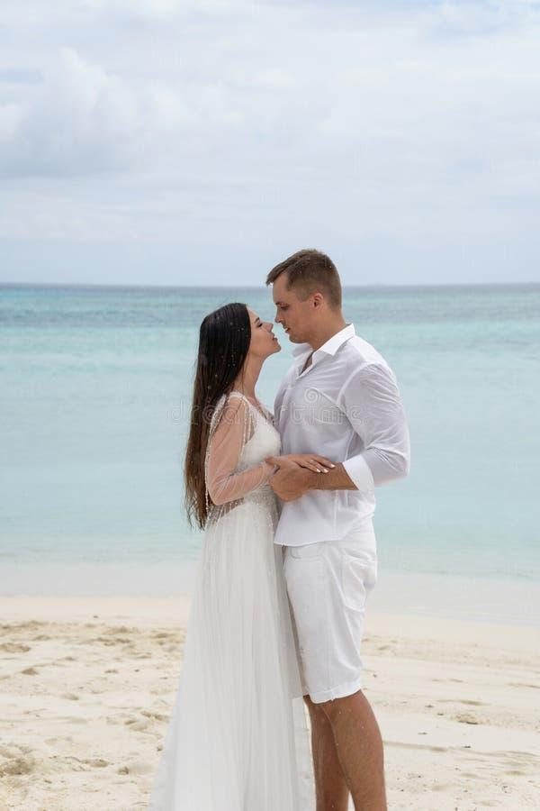 Os recém-casados estão abraçando em uma praia lindo com água branca da areia e da turquesa imagens de stock