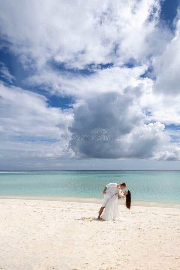 Os recém-casados estão dançando passionately em uma praia lindo com água branca da areia e da turquesa fotografia de stock