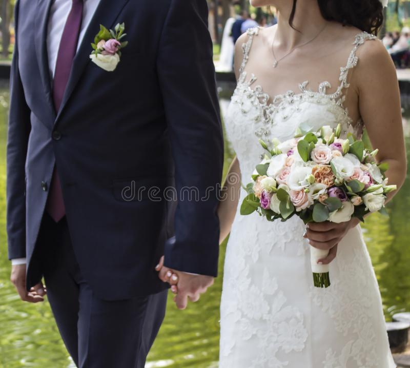 Os recém-casados que abraçam, a noiva são vestidos em um vestido de casamento branco clássico, o noivo são vestidos no terno pret imagens de stock royalty free