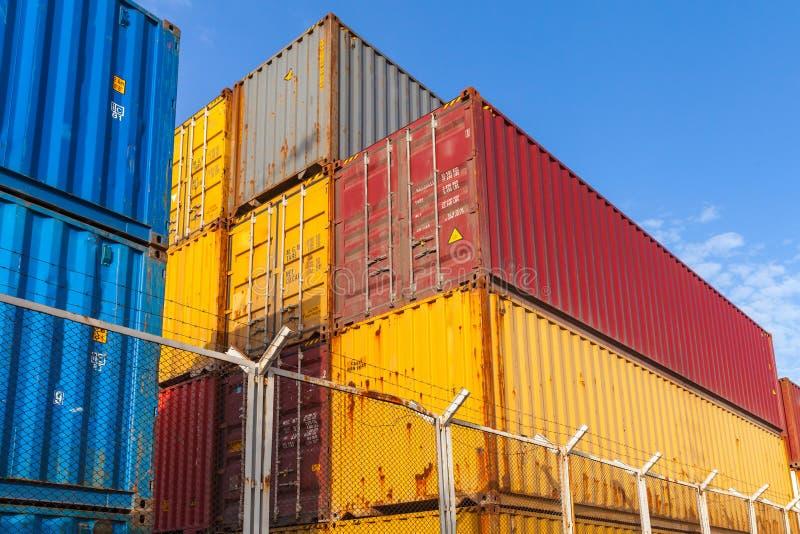 Os recipientes de carga coloridos são empilhados atrás da cerca do metal foto de stock