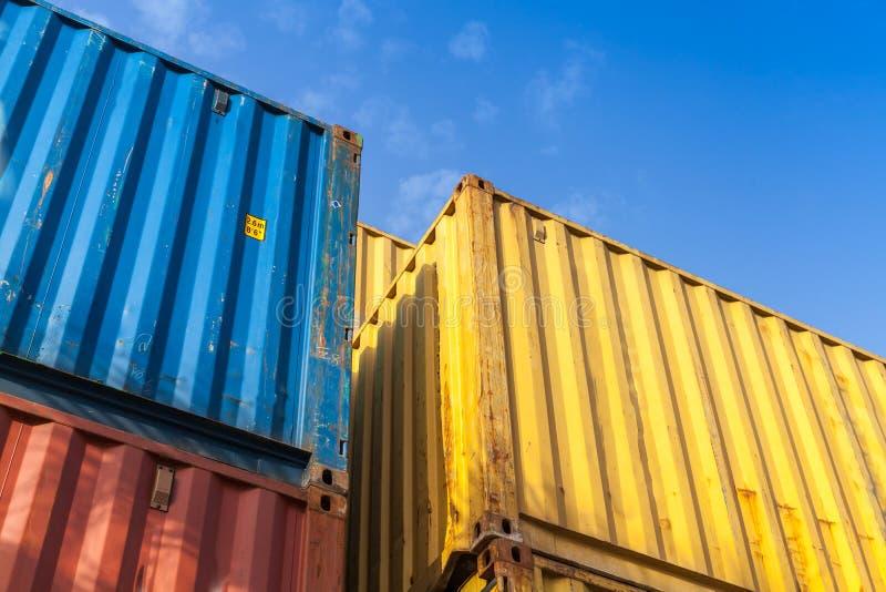 Os recipientes de carga coloridos são empilhados na área de armazenamento fotografia de stock