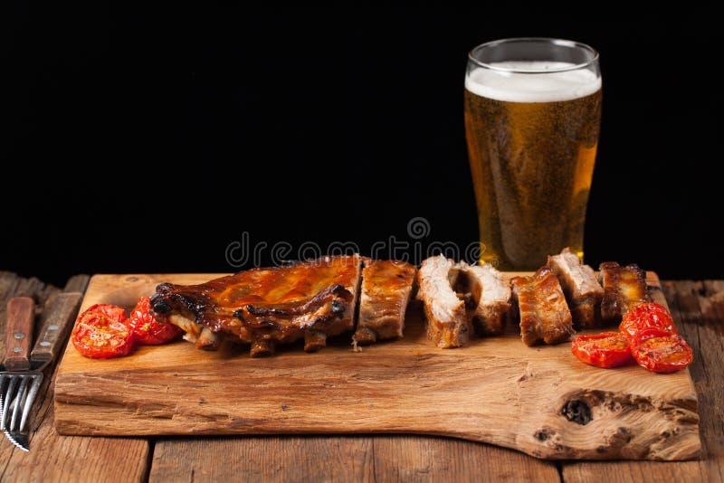 Os reforços de carne de porco no molho e no mel de assado cozeram tomates na tabela de madeira velha Carnes e cerveja clara no fu imagem de stock royalty free
