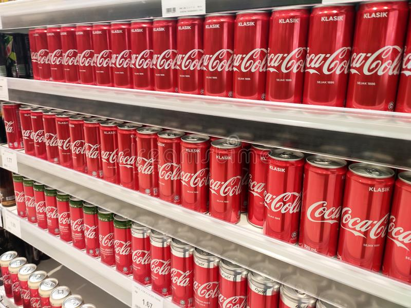 Os refrescos em umas latas são indicados em uma prateleira para a venda em um grande supermercado foto de stock