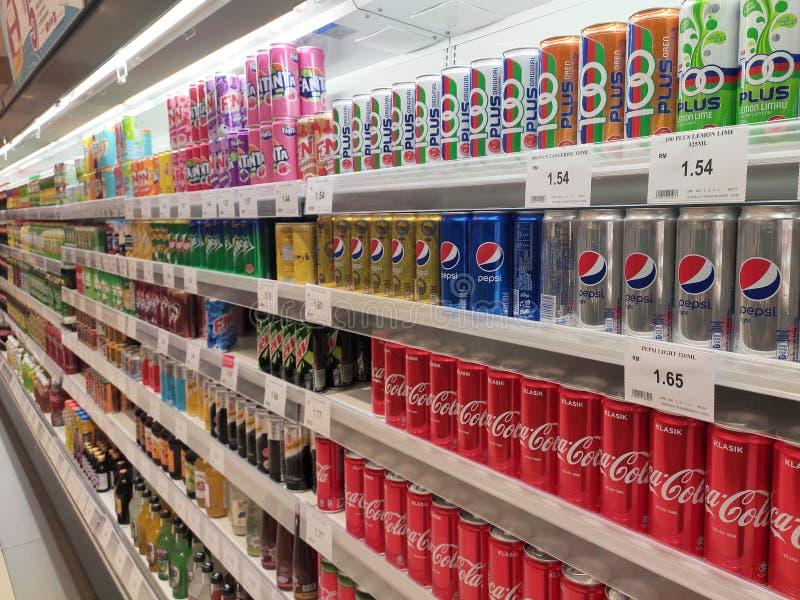 Os refrescos em umas latas são indicados em uma prateleira para a venda em um grande supermercado imagem de stock