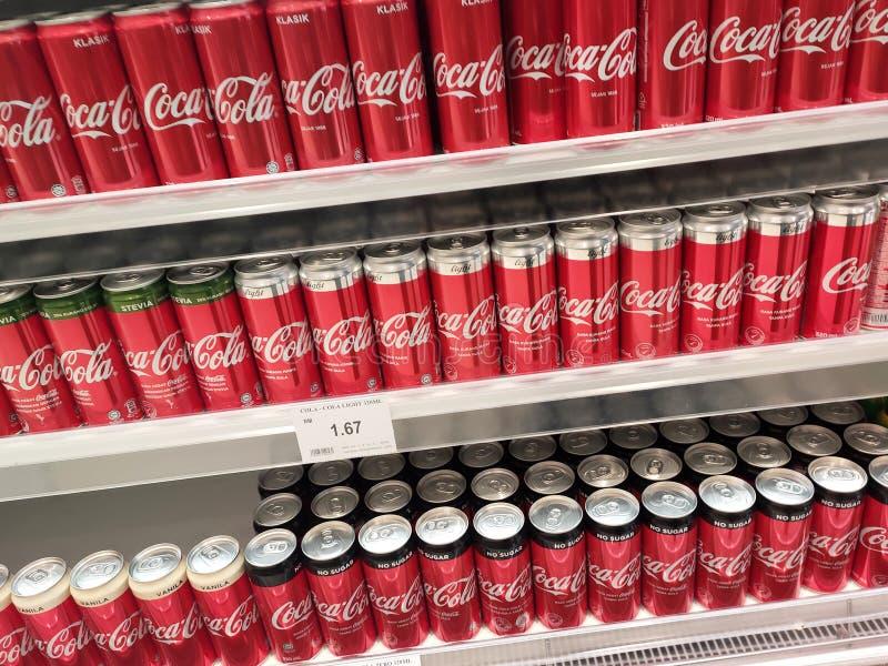 Os refrescos em umas latas são indicados em uma prateleira para a venda em um grande supermercado imagem de stock royalty free
